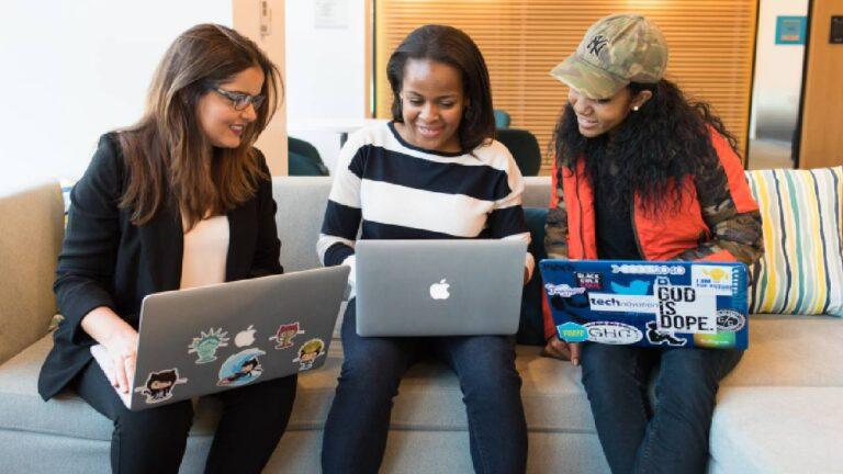 três mulheres sentadas à frente de computadores conversando sobre trabalho