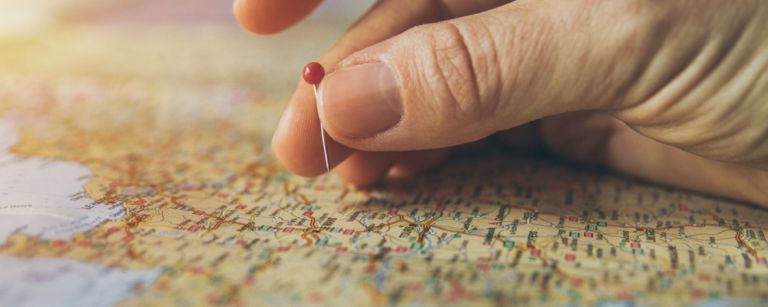 foto de um mapa sendo marcado com um alfinete. ilustrativo do conteúdo sobre mapeamento de ecossistemas de inovação